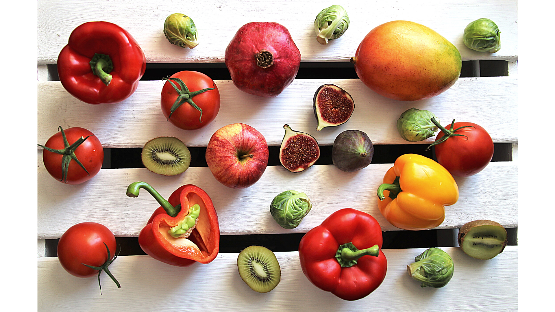 peppers, pomegranates, mangos, figs, and other fruit against a white background